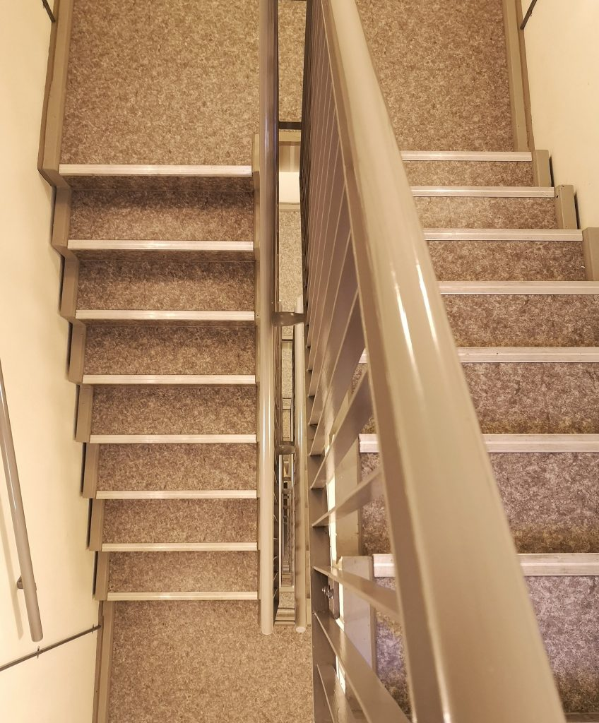 Bird's-eye view of a stairwell spiralling downwards.